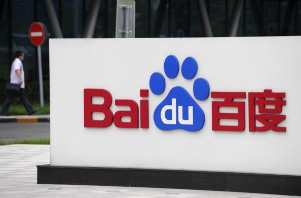 A man walks past the logo of Baidu at it